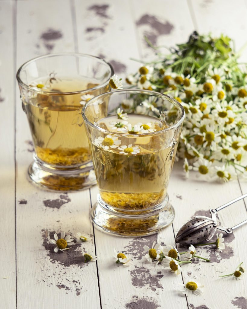 Two cups on a wooden bench filled with chamomile tea, garnished with chamomile flowers and surrounded by chamomile flowers.
