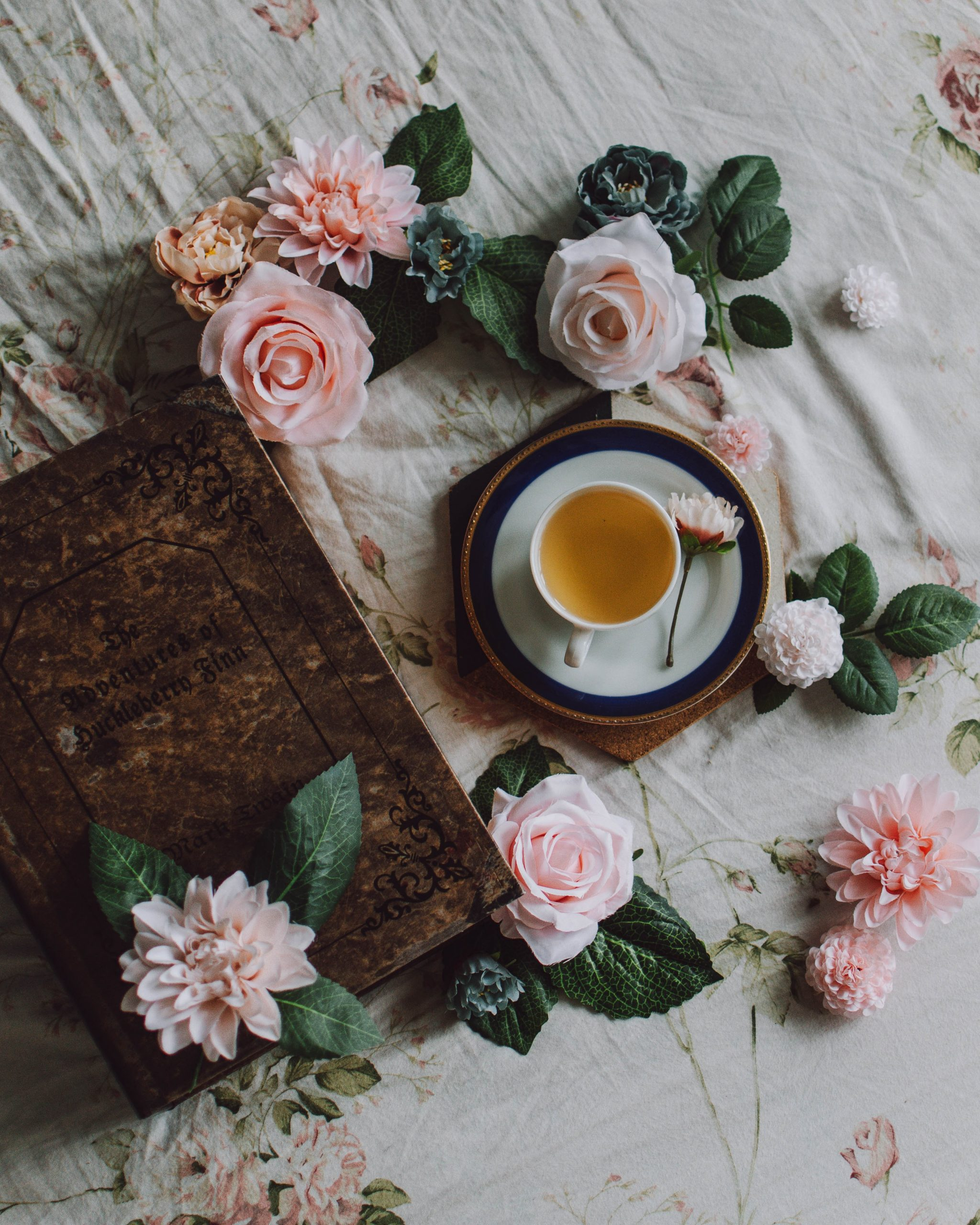 A book and various roses with a cup of rose tea placed on a saucer, all placed on a tablecloth