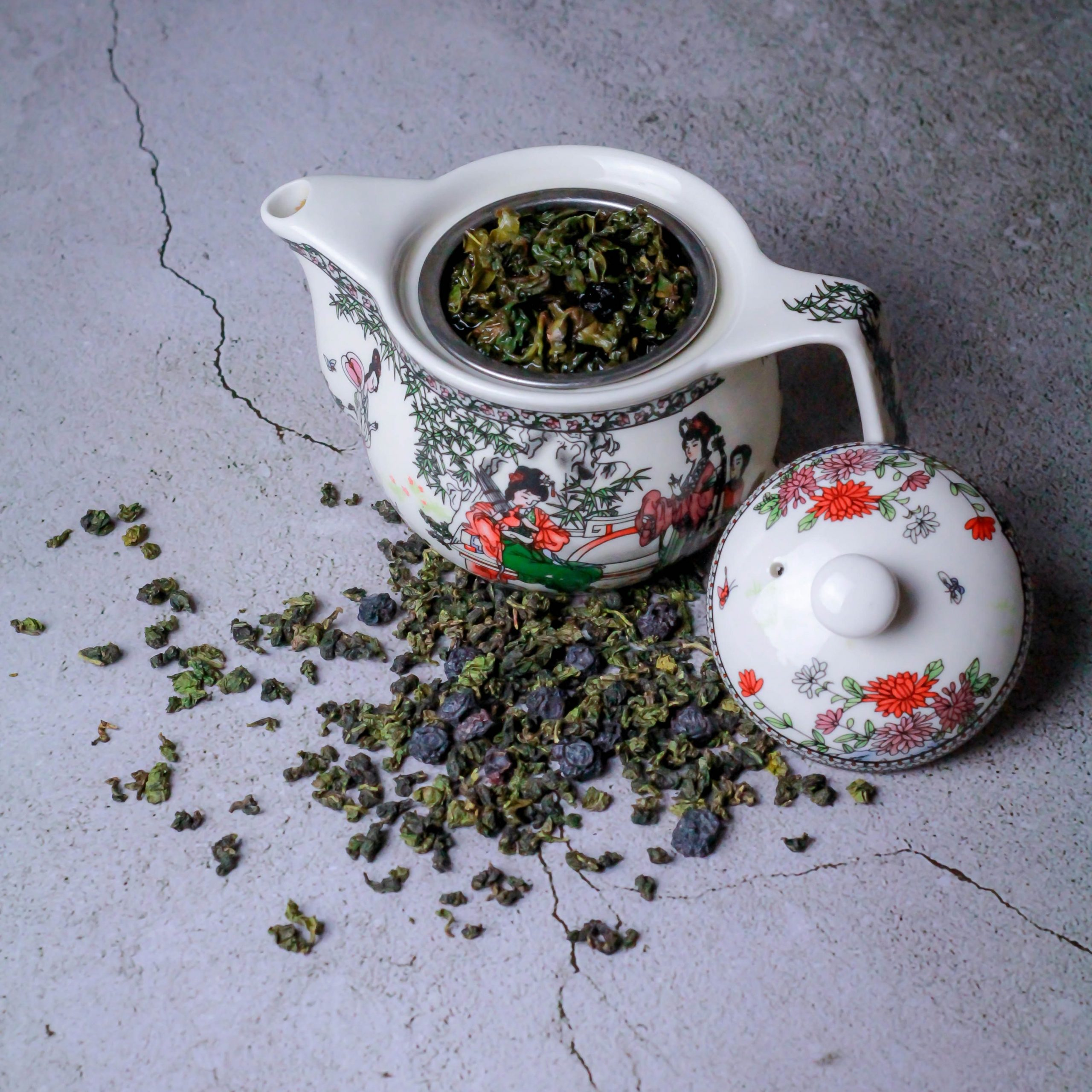 Teapot with printed art filled with Oolong tea leaves