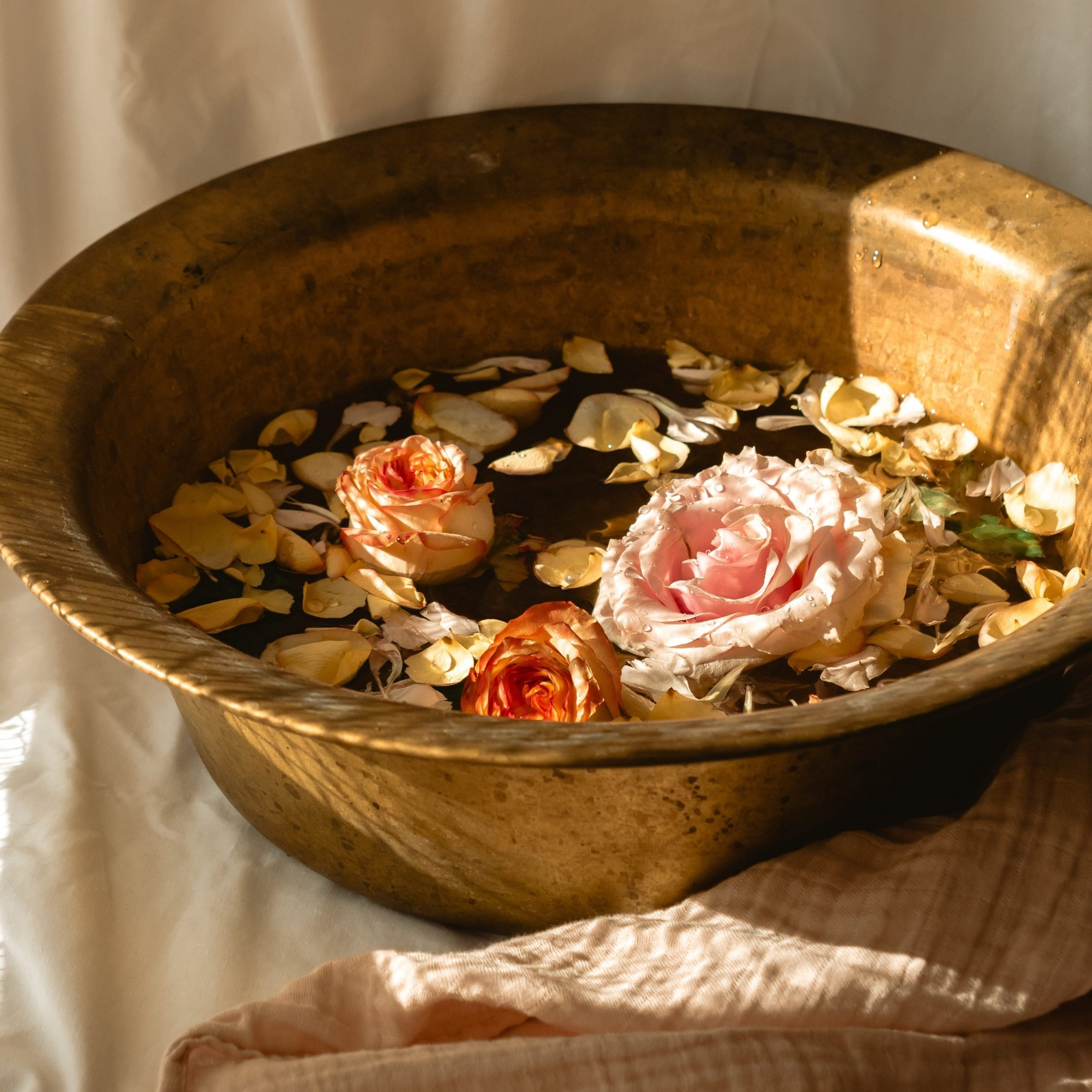 A bronze tub filled with water and 3 roses along with their petals.