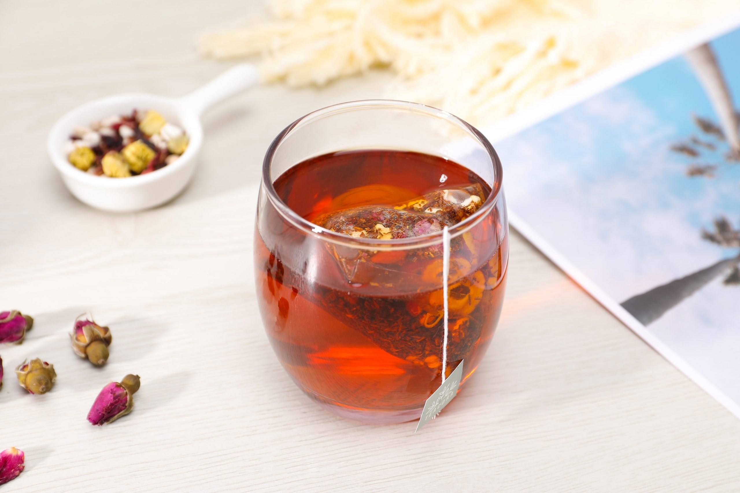 Focused shot of a glass cup filled with Rooibos Tea with a teabag in it.