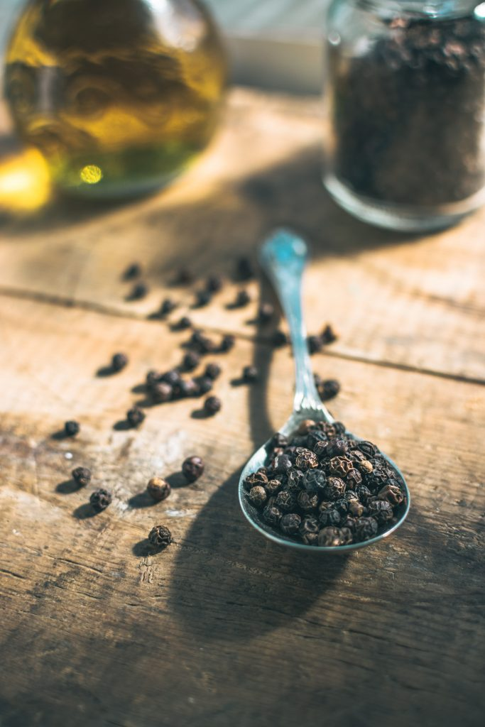 Spoonful of black pepper on a wooden table. Black pepper on display.