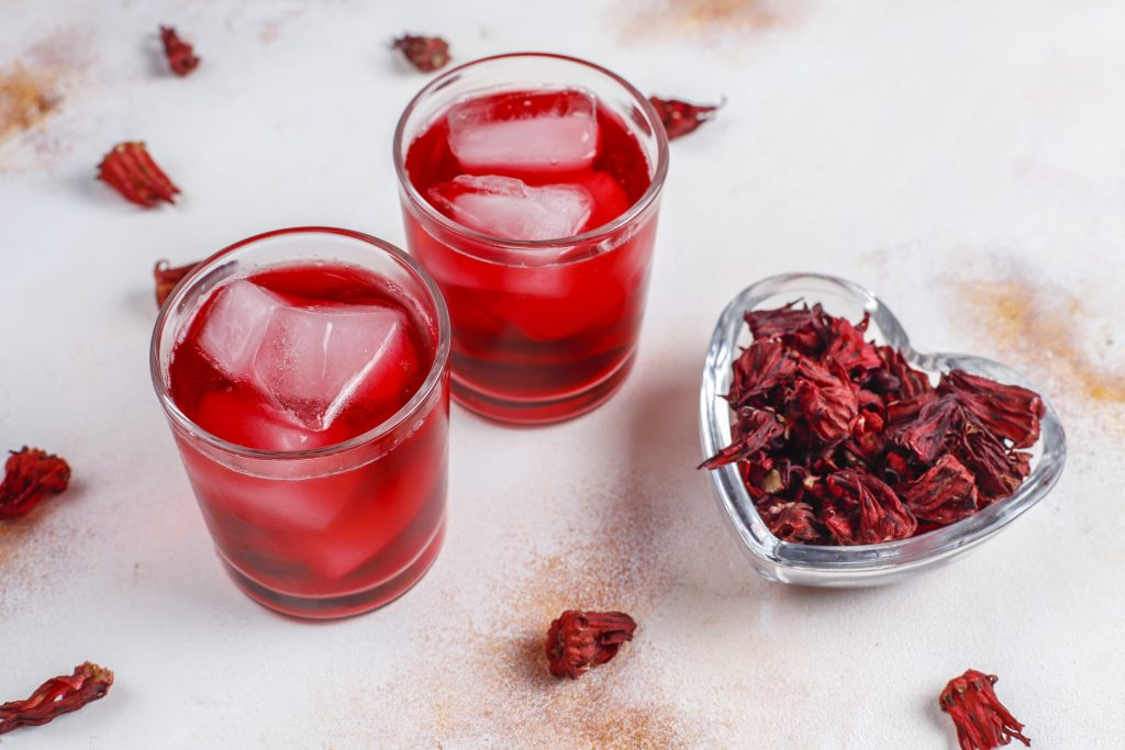 2 cups of hibiscus tea with ice and a heart-shaped bowl filled with hibiscus flowers