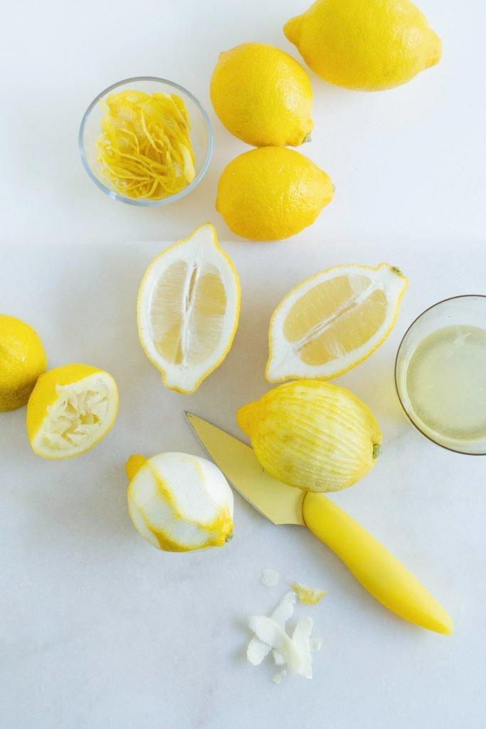 lemons and cup full of lemon peel/lemon zest with a yelklow knife