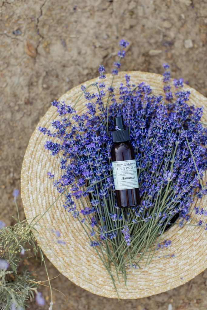 Black glass bottle and lavender flowers placed on round brown table